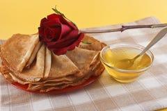 Pannkakor, blomma och honung på en servett Royaltyfria Bilder