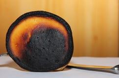 Pannkakor brände under matlagning på bakgrunden av en träyttersida Royaltyfria Foton