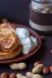 Pannkakor för frukost med kräm- muttrar och honung Arkivfoton