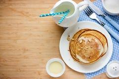 Pannkakor för frukost med sås och mjölkar på en träbackgroun Arkivbild