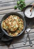 Pannkakor för potatis, för purjolök och för grön ärta i pannan på träbakgrund, bästa sikt Arkivbild