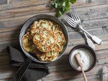 Pannkakor för potatis, för purjolök och för grön ärta i pannan på träbakgrund, bästa sikt royaltyfri foto