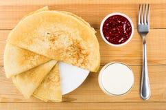 Pannkakor i platta, bunkar med hallondriftstopp, gaffel och mjölkar Royaltyfri Fotografi