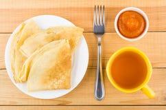 Pannkakor i platta, bunkar med persikan sitter fast, gaffeln och te Arkivfoto