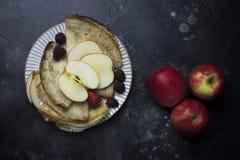 Pannkakor med äpplen, hallonet och jordgubben på den vita plattan på svart bakgrund royaltyfri bild