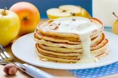 Pannkakor med äpplen, muttrar och sirap för frukost Royaltyfri Bild