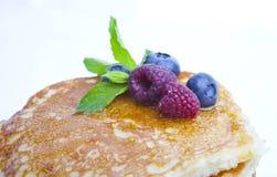 Pannkakor med bär, honung och mintkaramellen Arkivfoto
