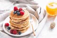 Pannkakor med bär och honung royaltyfri foto