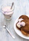 Pannkakor med bäryoghurt i en vit bunke på en trätabell Yoghurt med vinbär i exponeringsglaset royaltyfri fotografi