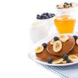 Pannkakor med bananen och blåbär, yoghurt och mysli som isoleras Royaltyfria Bilder