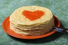 Pannkakor med den röda kaviaren i form av hjärta royaltyfria foton