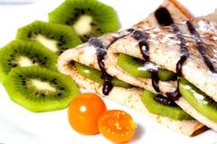 Pannkakor med en kiwi, fizalisy och choklad Royaltyfria Bilder