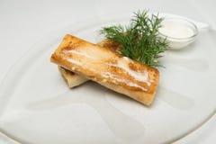 Pannkakor med fyllning som täckas med smör på den glass plattan Omgivet med gräddfil och dill arkivfoto
