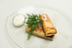 Pannkakor med fyllning som täckas med smör på den glass plattan Omgivet med gräddfil och dill royaltyfri bild