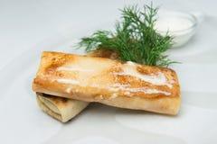 Pannkakor med fyllning som täckas med smör på den glass plattan Omgivet med gräddfil och dill fotografering för bildbyråer