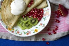 Pannkakor med gräddfil, kiwi och pomgranate Fotografering för Bildbyråer