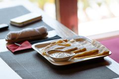 Pannkakor med gräddfil på den vita fyrkantiga plattan på tabellen royaltyfri fotografi