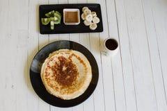 Pannkakor med honung och frukt arkivfoto