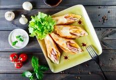 Pannkakor med huggen av skinka och ost som dekoreras med grönsallat på mörkt träbakgrundsslut upp Royaltyfria Foton