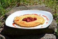Pannkakor med jordgubbar och kräm i trädgården Arkivbild