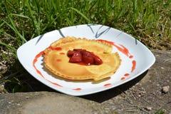 Pannkakor med jordgubbar på den vita plattan Royaltyfri Foto