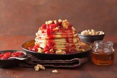 Pannkakor med jordgubbedriftstopp och valnötter smaklig efterrätt Royaltyfri Foto