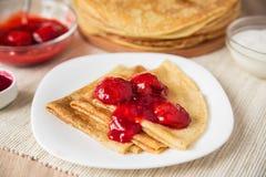 Pannkakor med jordgubbesås på en vit platta Arkivfoton