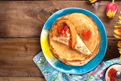 Pannkakor med kaviaren och sm?r, en bukett av nya tulpan och en tr?bakgrund Traditionell rysk mat f?r karneval ?verkant arkivfoto