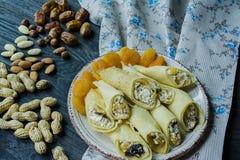 Pannkakor med keso, katrinplommoner, torkade aprikors och russin Slapp fokus m?rkt tr? f?r bakgrund royaltyfria bilder