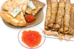Pannkakor med ost, den röda kaviaren och stekt kyckling lappar på en w Royaltyfri Foto
