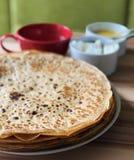 Pannkakor med vita ost för lokal bihonung och te och skedar på bakgrunden på fokus Arkivfoto