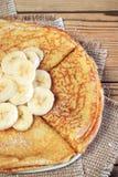 Pannkakor som dammas av med pudrat socker, med en banan Royaltyfri Foto