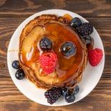 Pannkakor som täckas av honung med blåbär och jordgubbar på träbakgrund close upp arkivfoton