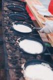 Pannkakorna stekas i en panna på kolen arkivbilder