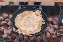 Pannkakorna stekas i en panna på kolen arkivbild