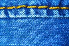 Panno delle blue jeans con la scenetta di struttura del fondo della cucitura Immagini Stock Libere da Diritti