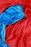 Panno di seta blu e rosso degli ambiti di provenienza astratti ondulati Immagini Stock