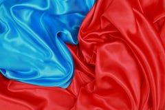 Panno di seta blu e rosso degli ambiti di provenienza astratti ondulati Fotografia Stock