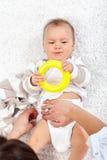 Pannolini cambianti su una neonata Fotografie Stock