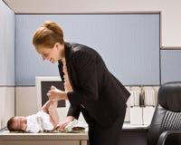 Pannolino cambiante del bambino della donna di affari allo scrittorio Immagine Stock