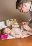 Pannolino cambiante del padre del bambino adorabile Fotografia Stock