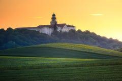 Pannonhalma Archabbey con el campo de trigo el tiempo de la puesta del sol Foto de archivo libre de regalías