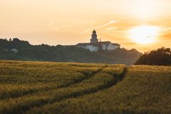 Pannonhalma Archabbey with wheat field and path on sunset in Hungary royalty free stock photography