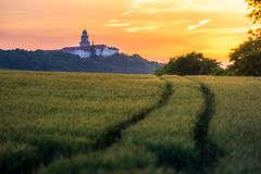 Pannonhalma Archabbey with wheat field and path on sunset in Hungary royalty free stock image
