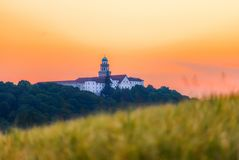 Pannonhalma Archabbey with wheat field on sunset in Hungary royalty free stock photo