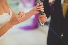 Panny młodej mienia pierścionek podczas ślubnej ceremonii i fornal, dalej Obrazy Royalty Free