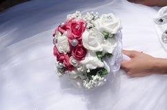 Panny młodej ręka w białej sukni z bukietem bielu i menchii róże Obrazy Royalty Free