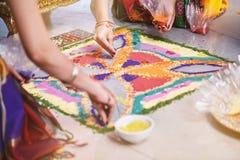 Panny młodej ` s przyjaciel pomaga barwić tradycyjną ryżową sztukę Rangoli na podłoga dla indyjskiego ślubu Zdjęcie Stock