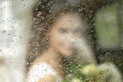 Panny młodej sylwetka w ślubnej sukni z bukietem kwiaty przez szkła w podeszczowych kroplach zdjęcia stock