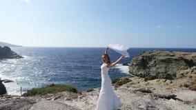 Panny młodej szczęśliwi stojaki na seashore pod ślubną przesłoną trzepocze w wiatrze Pojęcie szczęśliwy małżeństwo a i zdjęcie wideo